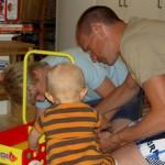 Jonatan och pappa monterar ihop gåvagnen och Tilde tittar på.